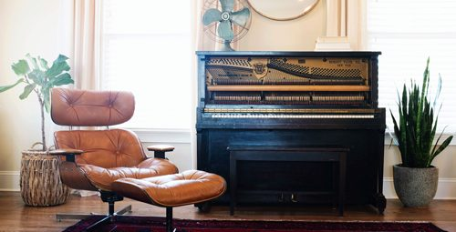 A room with a chair and piano