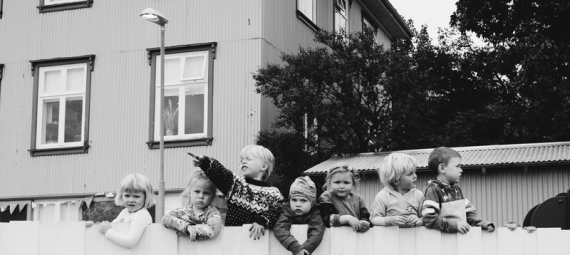Children looking over a fence.