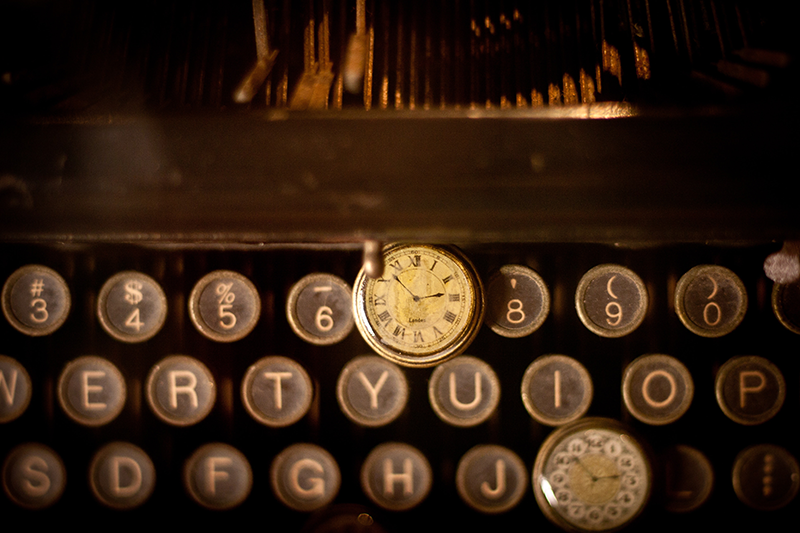 Old typewriter with a time piece draped over it.