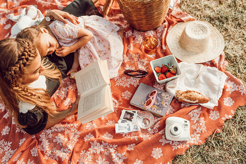 Mother and daughter reading a book together at a picnic.