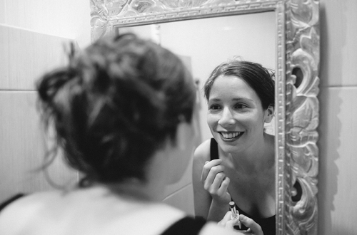 Woman smiling at herself in mirror.